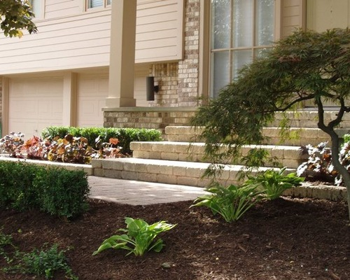Brick steps in front of house with beautiful landscaping