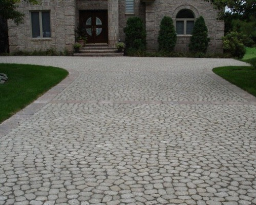 expansive brick driveway in front of house fits multiple cars