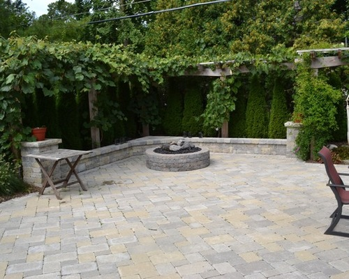 Brick backyard patio with pergola covered in green plants and firepit
