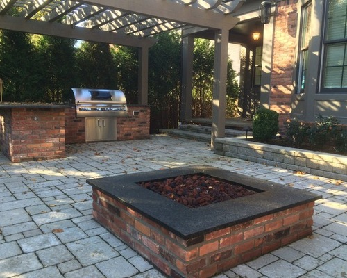 Square brick firepit with black top and an outdoor kitchen