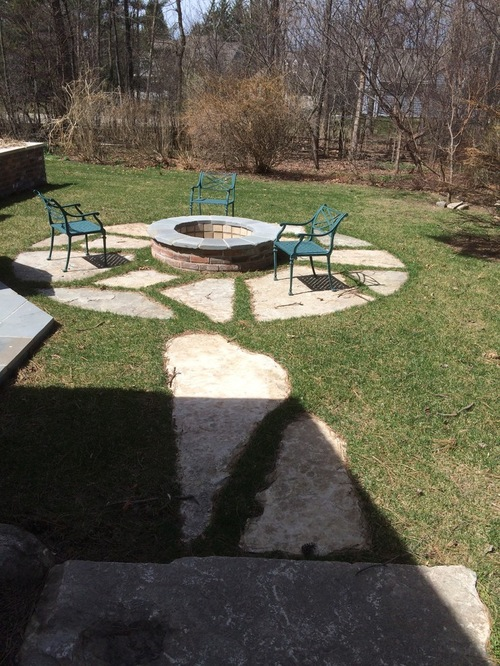 Backyard walkway leading to circular firepit and chairs