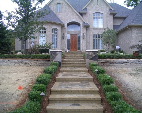 luxury stone home with steps lined with shrubs