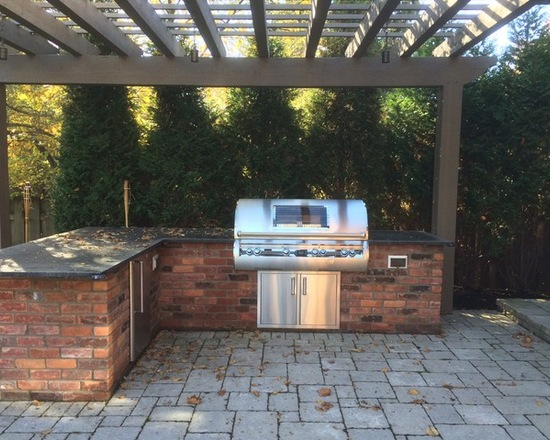 stainless steel barbecue in outdoor brick kitchen with pergola