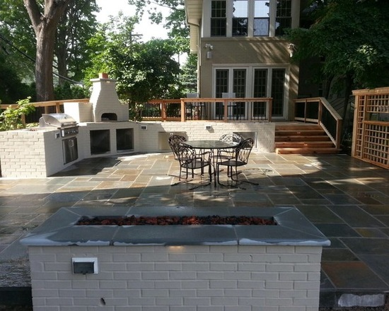 outdoor kitchen and gathering area with table and modern firepit
