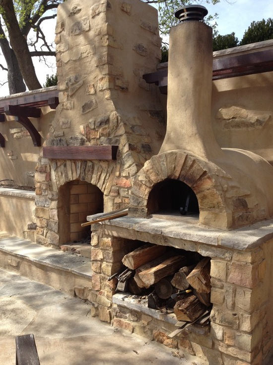 outdoor stone fireplace with pizza oven and wood storage
