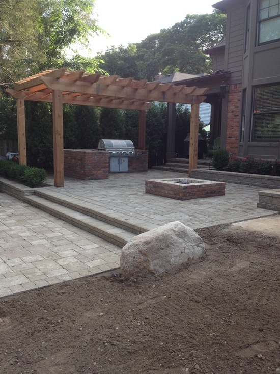 pergola over natural stone patio and outdoor kitchen