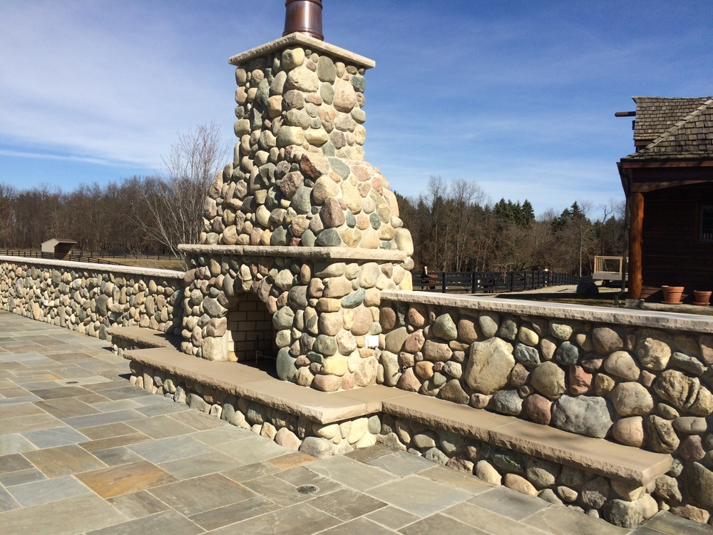 Natural stone fireplace outside on a clear day