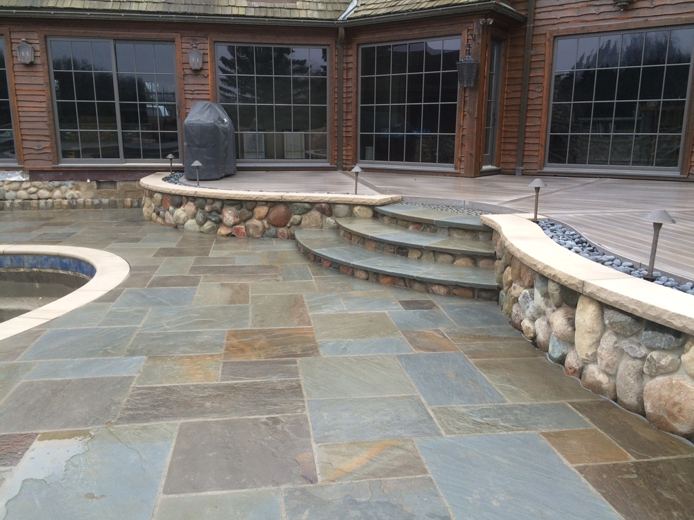 brick house with a bluestone patio and stairs