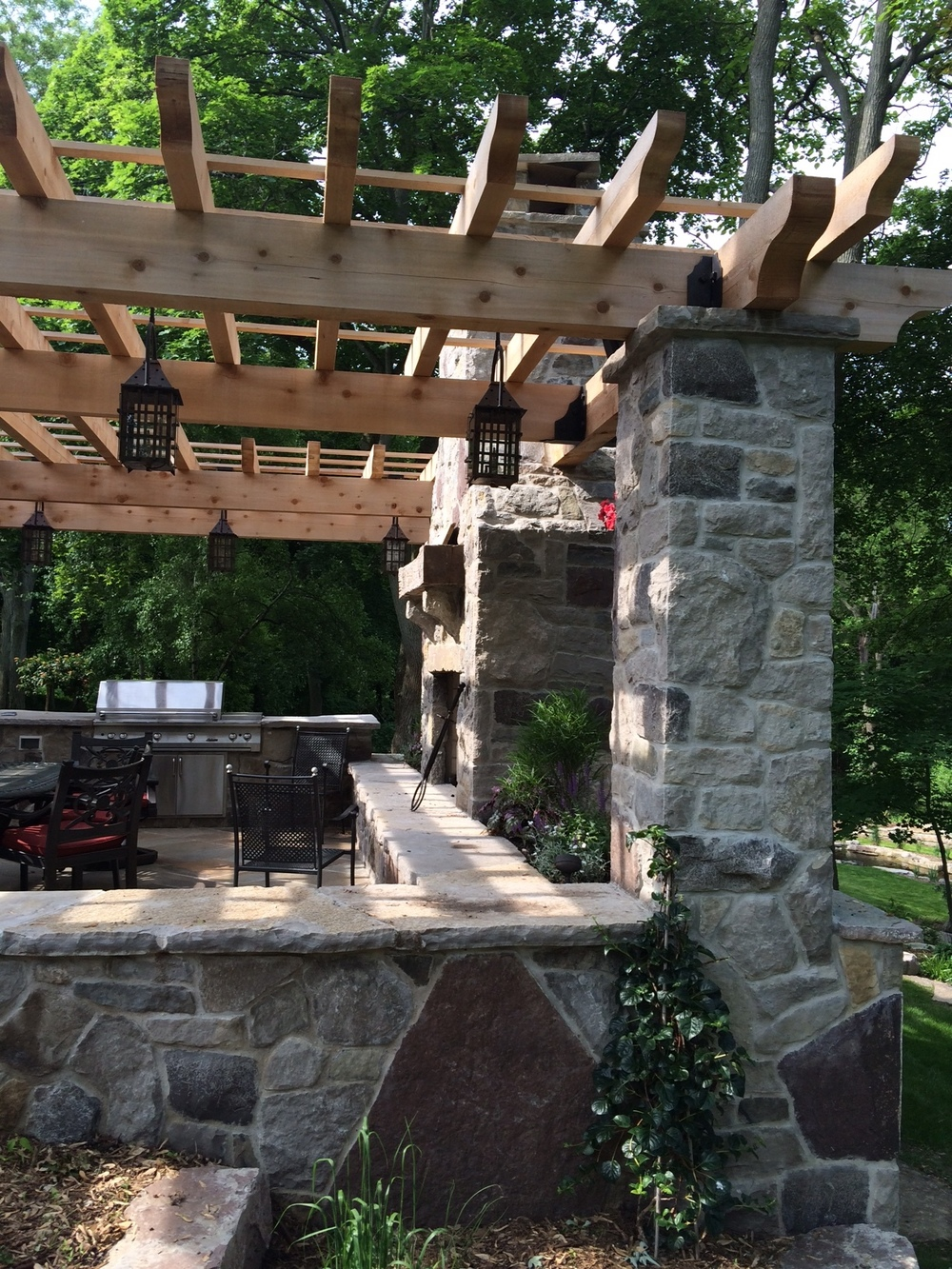 Wooden pergola and natural stone outdoor seating space