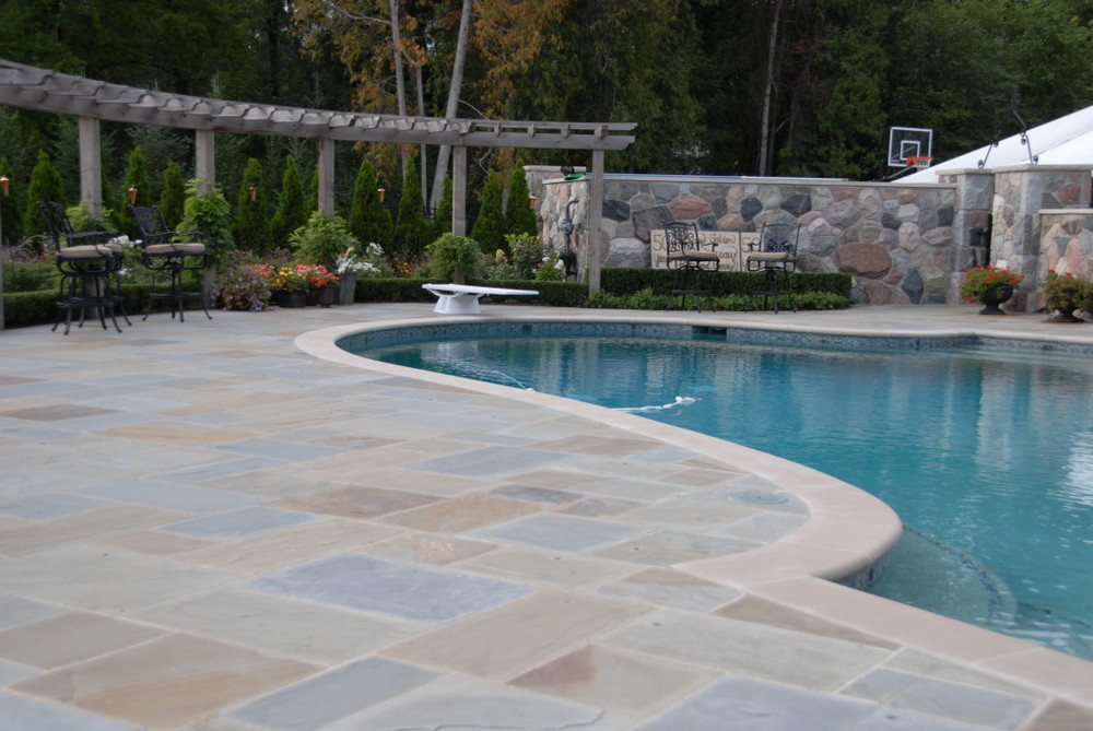 wood pergola and a natural bluestone pool deck