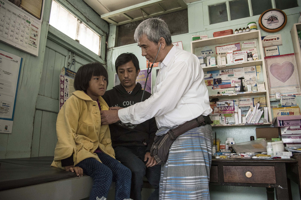 Doctor Maung Maung Aye examines Khan Pyae Shan, a 9-year old girl who is HIV-positive. Ko Ko Oo, the girl's father stands by her. Mogok, 2015. Photo © Thierry Falise.
