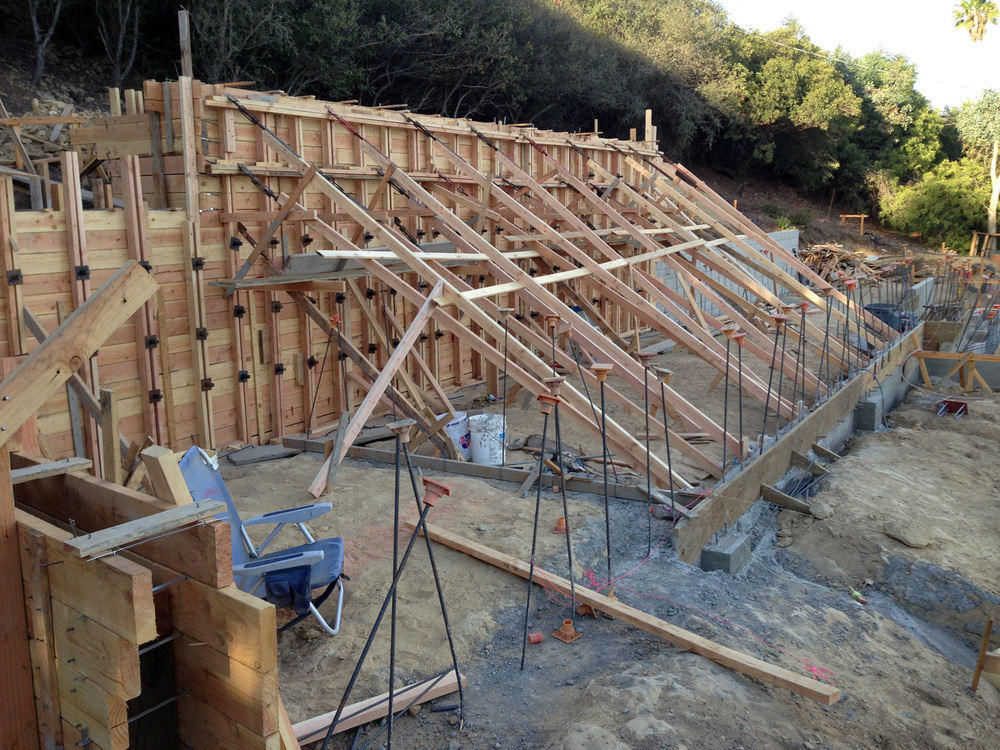 Concrete Board formed wall. All the horizontal  2x6s  form boards  were reused after the pour for roof rafters.