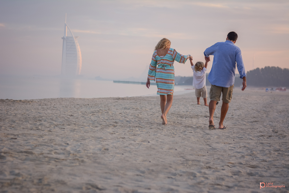 Beach Family and Maternity Session in Dubai mother and father holding their little son's hands by the beach as they swing him in the air
