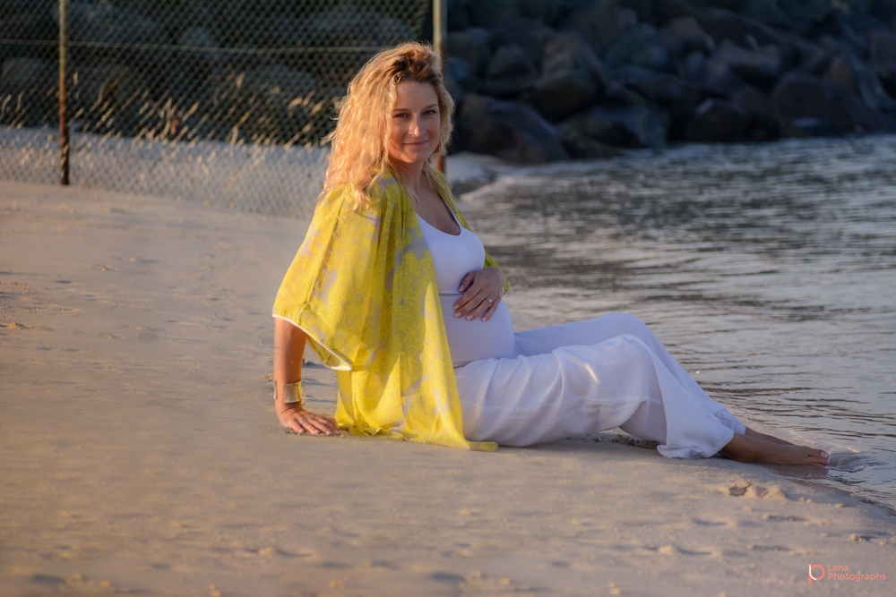 Beach Family and Maternity Session in Dubai portrait of a pregnant woman sitting along the shore wearing a yellow shirt