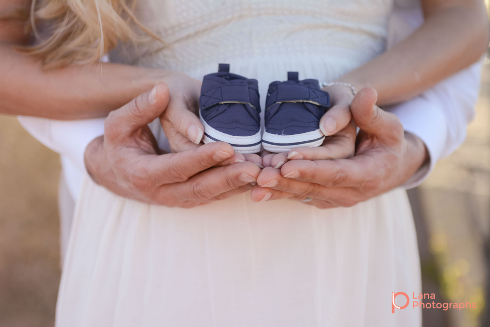 Dubai Maternity Photography portrait of expectant couple posing while holding their future son's shoes in their hands