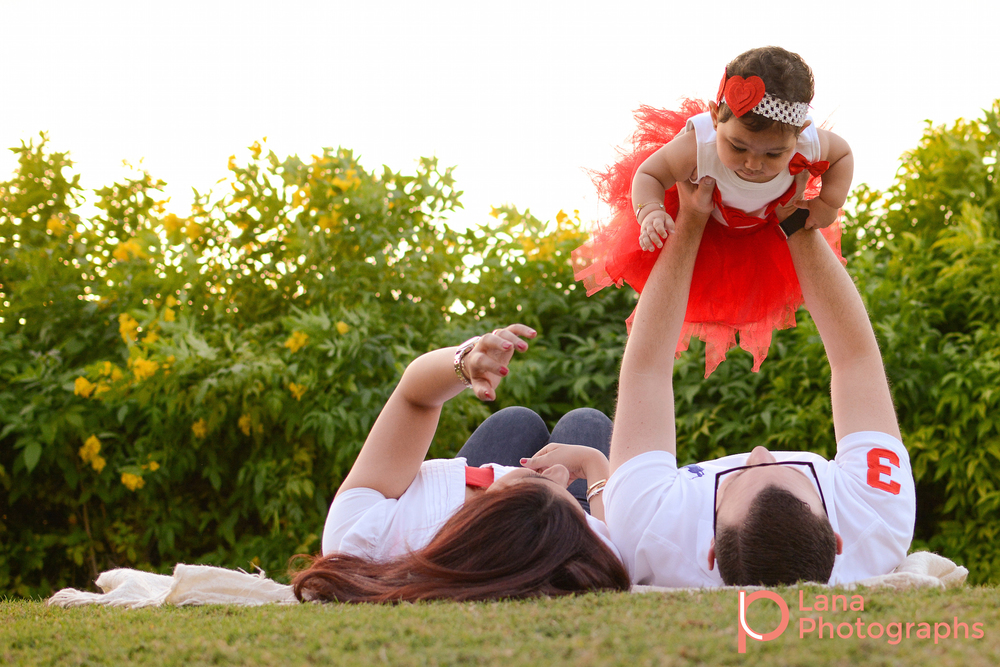 Dubai Family Photography family portrait of a family of three wearing red and white in the park laying down in the grass and lifting little girl in the air