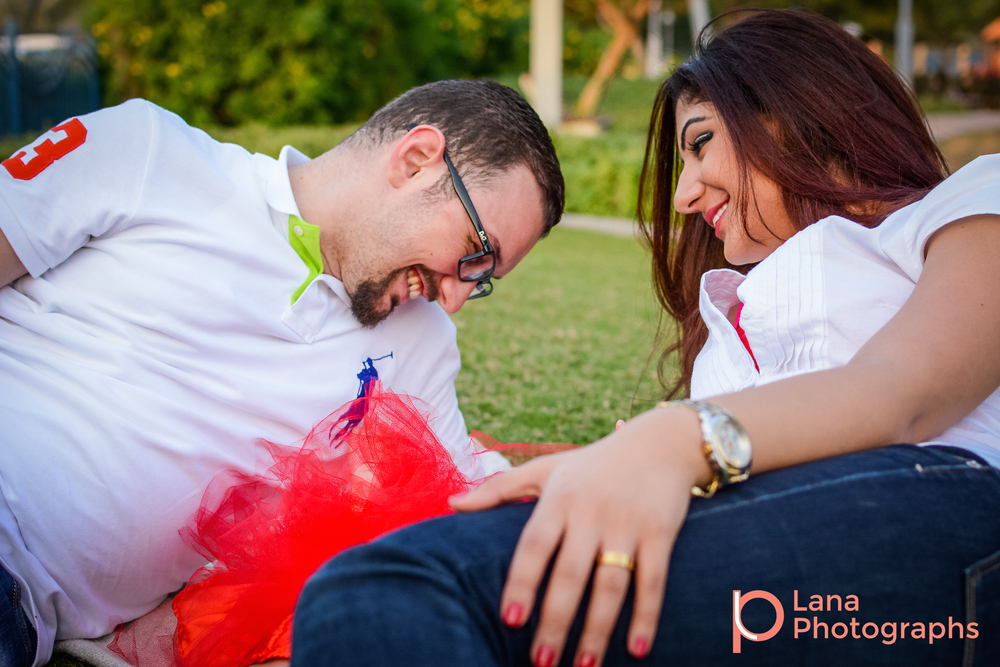 Dubai Family Photography family portrait of a family of three wearing red and white in the park laying down in the grass and lifting little girl in the air with mom looking at father