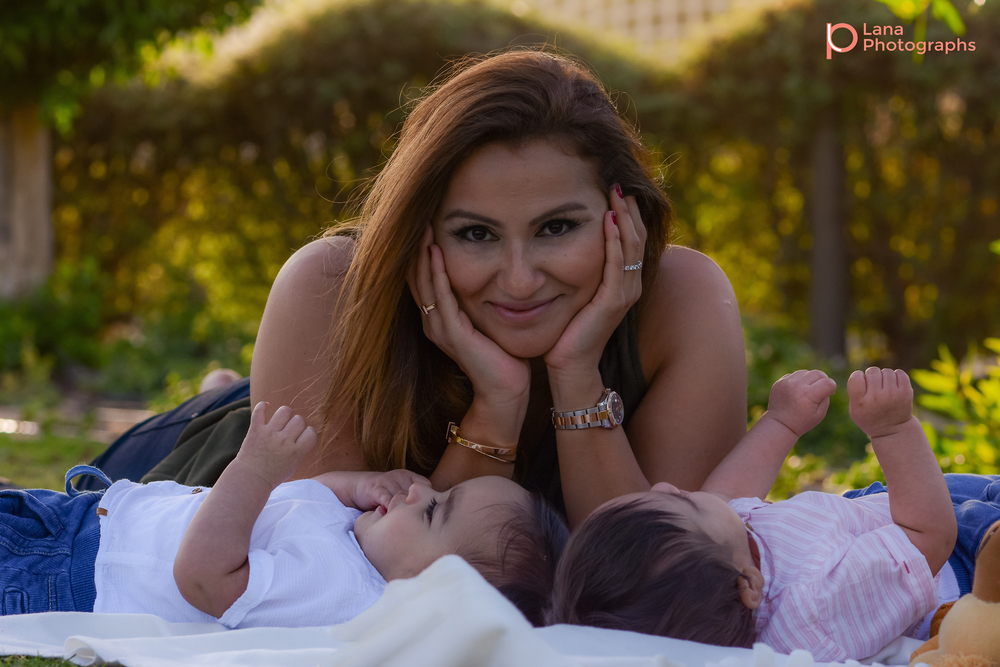 Dubai Family Photography portrait of mother posing with her twins in the grass in the park