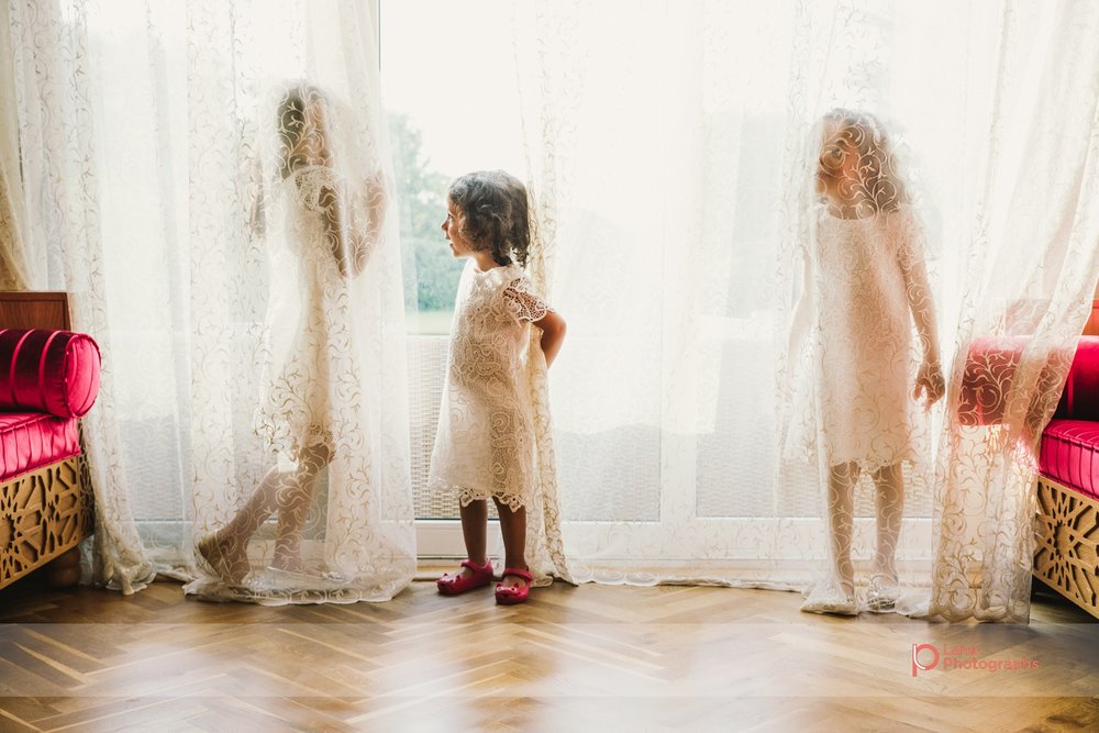 Lana Photographs Family Photographer Dubai Top Family Photographers three girls playing inside the curtains by the window