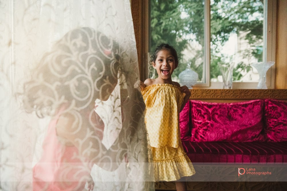 Lana Photographs Family Photographer Dubai Top Family Photographers girl in yellow dress dancing by the window