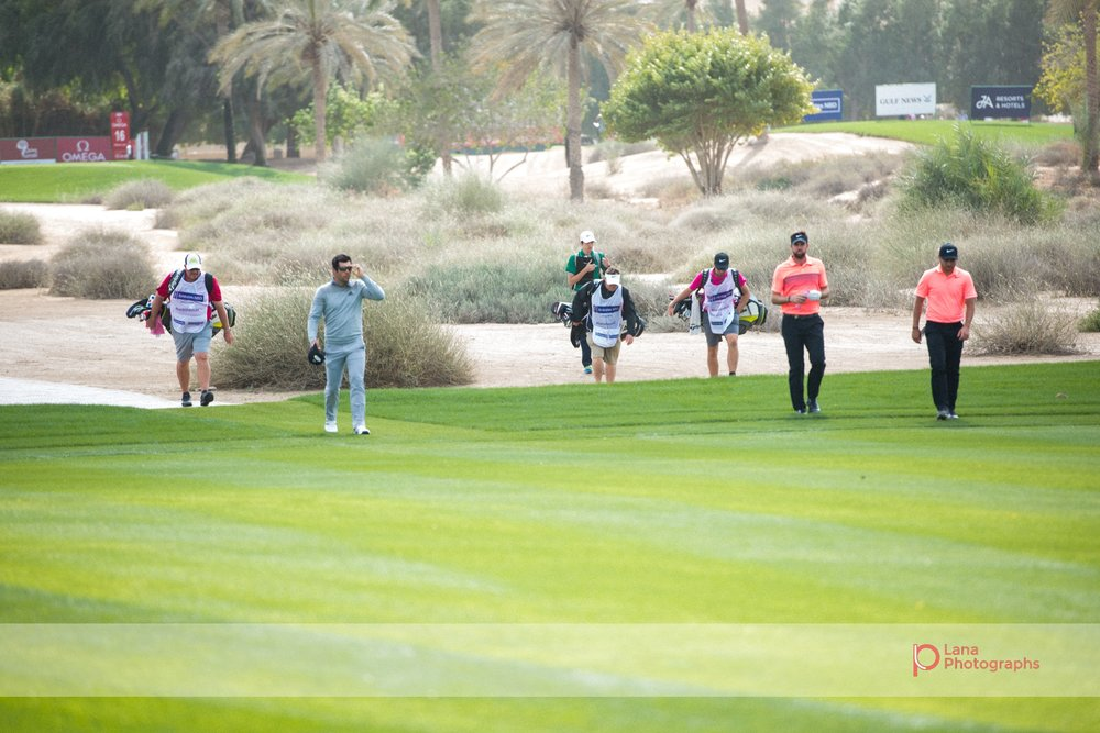 Caddie players join their golfing pros as they walk across the grounds of the Emirates Golf Course in February 2017