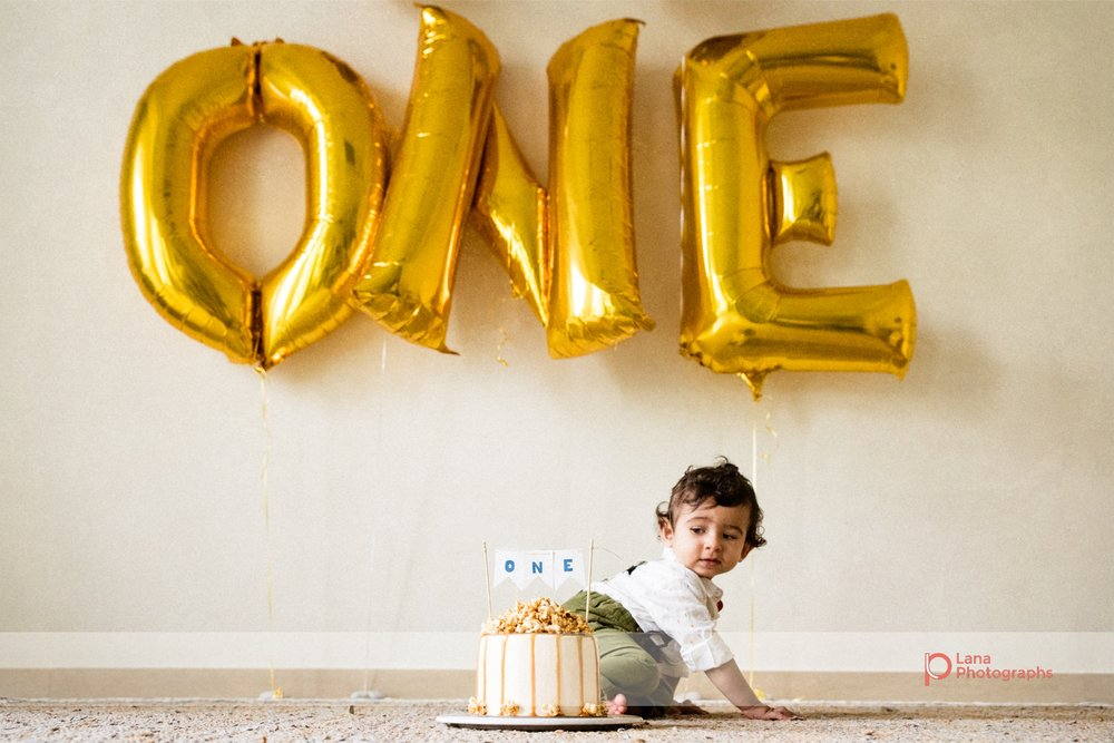 Cake Smash Dubai Baby poses with birthday cake and balloons
