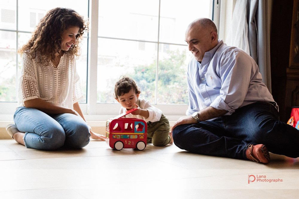 mother and father sit with their one year old baby boy next to the window and play with his toy truck