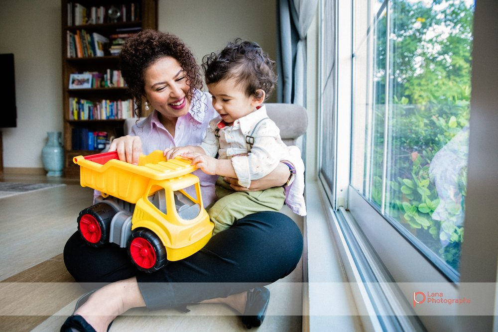 baby and his auntie sit next to the window and play with his yellow toy truck