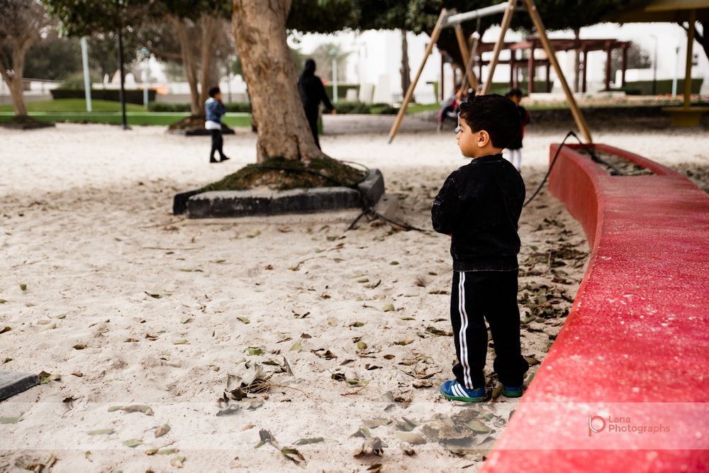 Dubai Family Photographer little boy standing in the sand by a red curb in Umm suqeim park Dubai