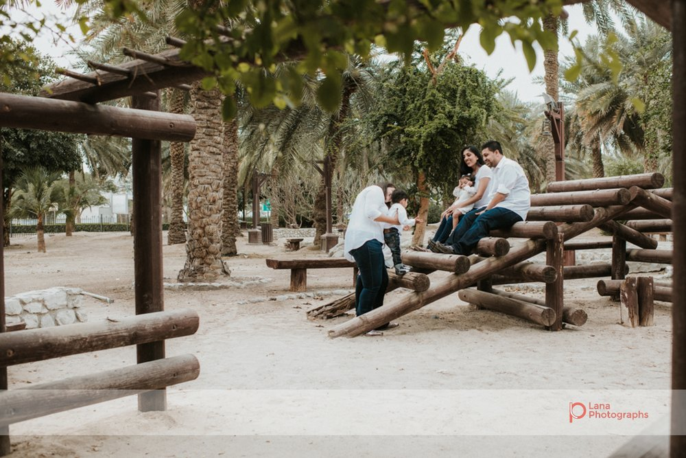 Lana Photographs Family Photographer Dubai Top Family Photographers family sitting in the park on benches