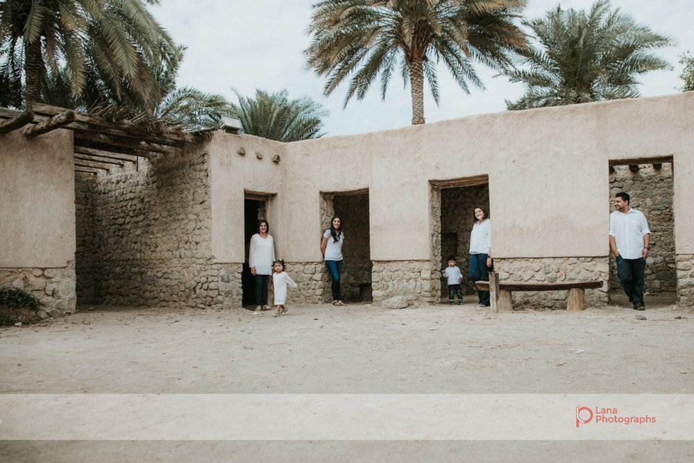 Lana Photographs Family Photographer Dubai Top Family Photographers family of four posing inside door frames under palm trees