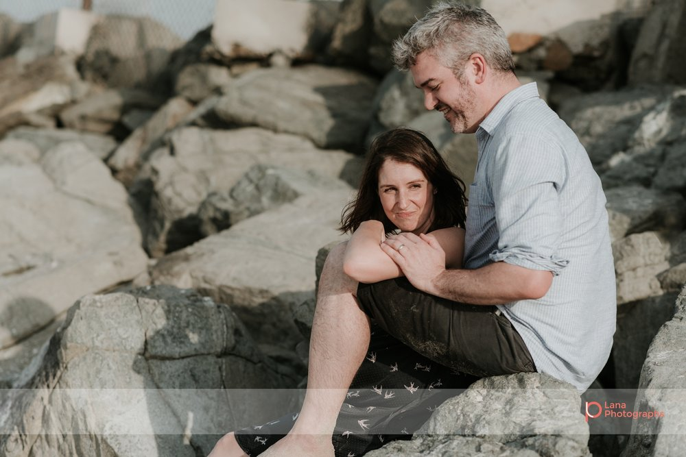 Lana Photographs Maternity Photography Dubai Professional Maternity Photographer husband and wife sitting on the rocks by the beach