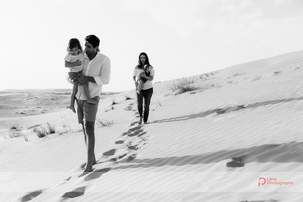 Lana Photographs Family Photographer Dubai Top Family Photographers family of four walking in the desert