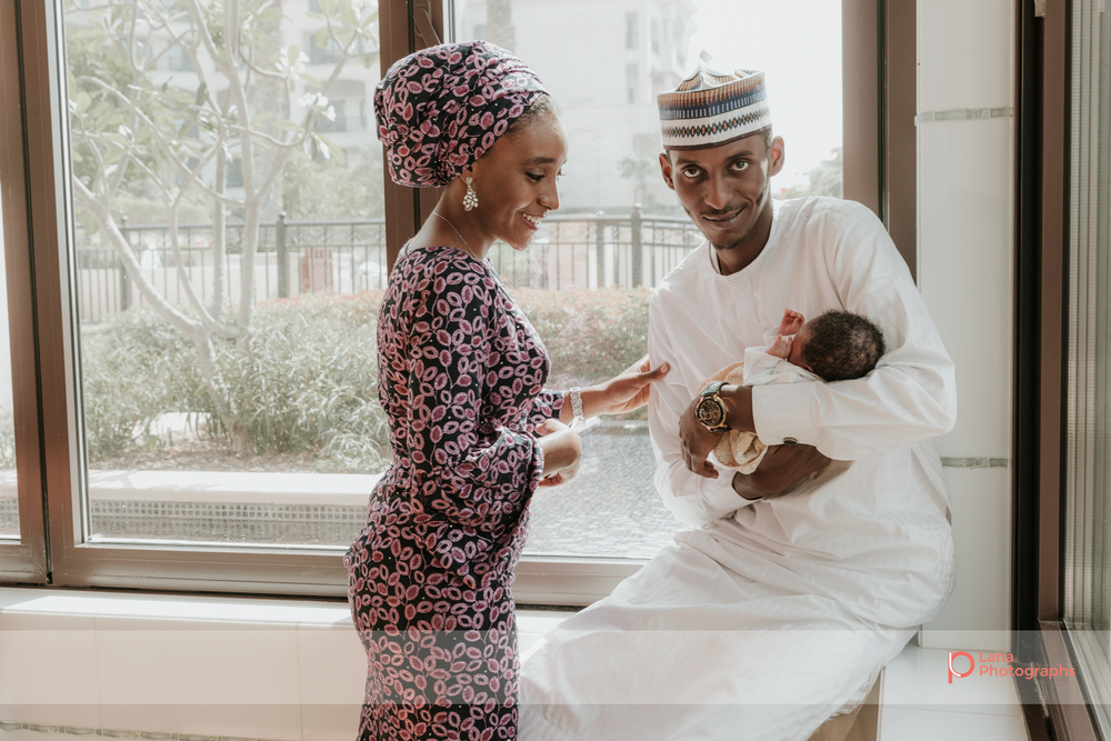Newborn Baby Photography Abu Dhabi Hospital Portrait of a newborn baby being cradled by her aunt and uncle in beautiful window light