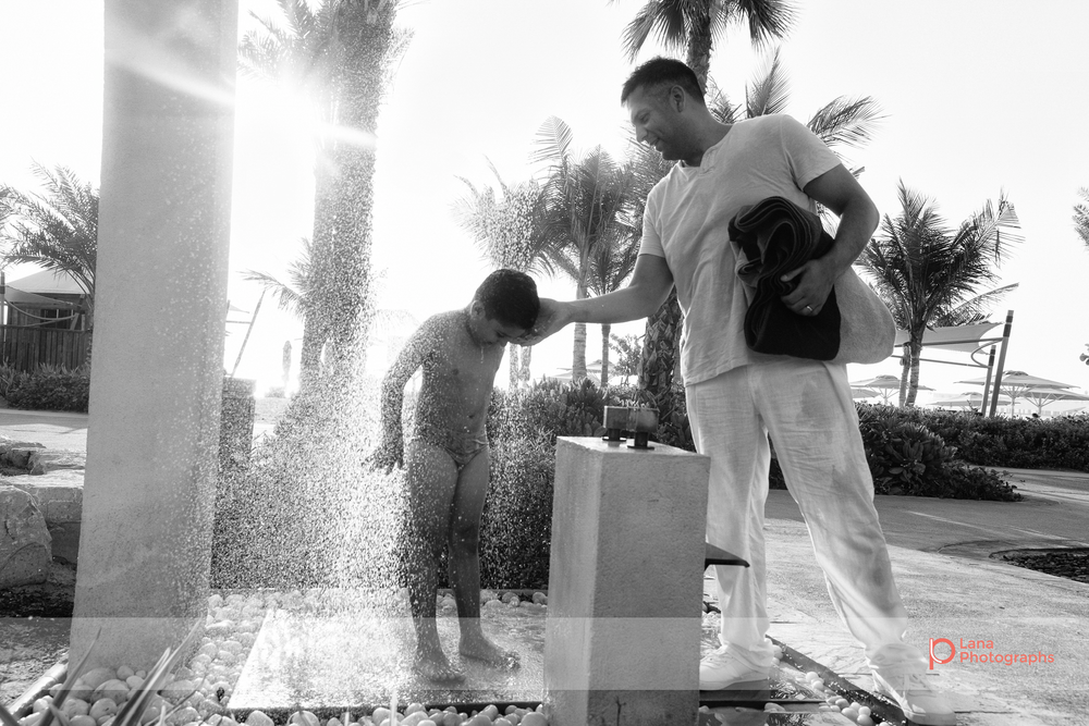 Lana Photographs Dubai Family Photography beach photoshoot father washes sand off son