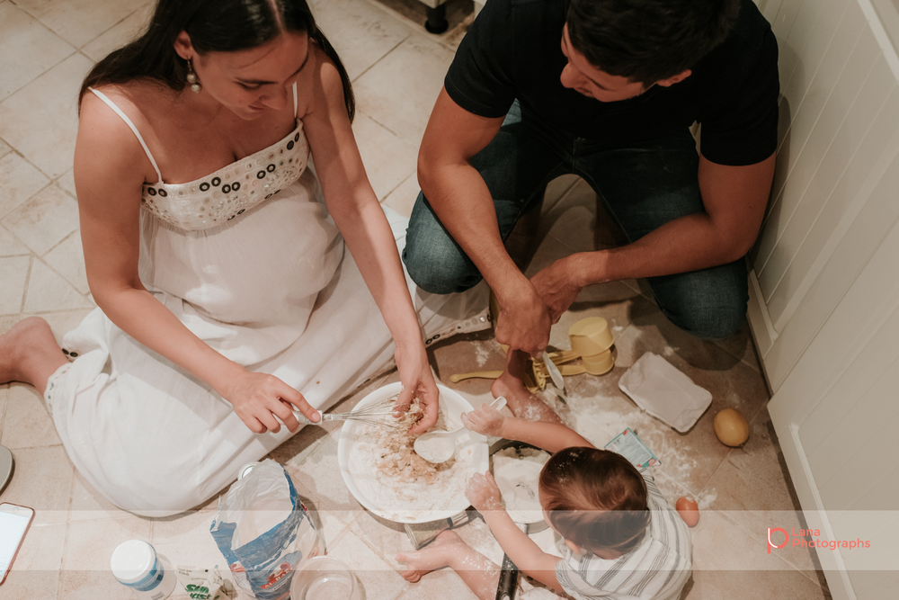 Lana Photographs Dubai Family Photographer image of family of three sitting on kitchen floor and preparing baking ingredients