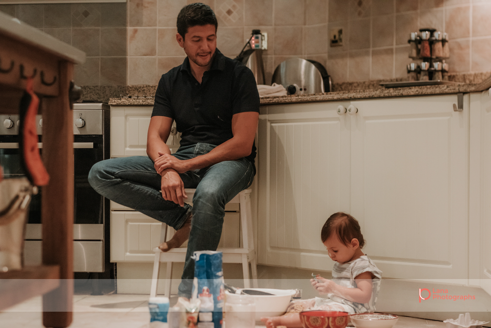 Lana Photographs Dubai Family Photographer image of father sitting on kitchen stool watching this little girl playing with baking flour on the floor
