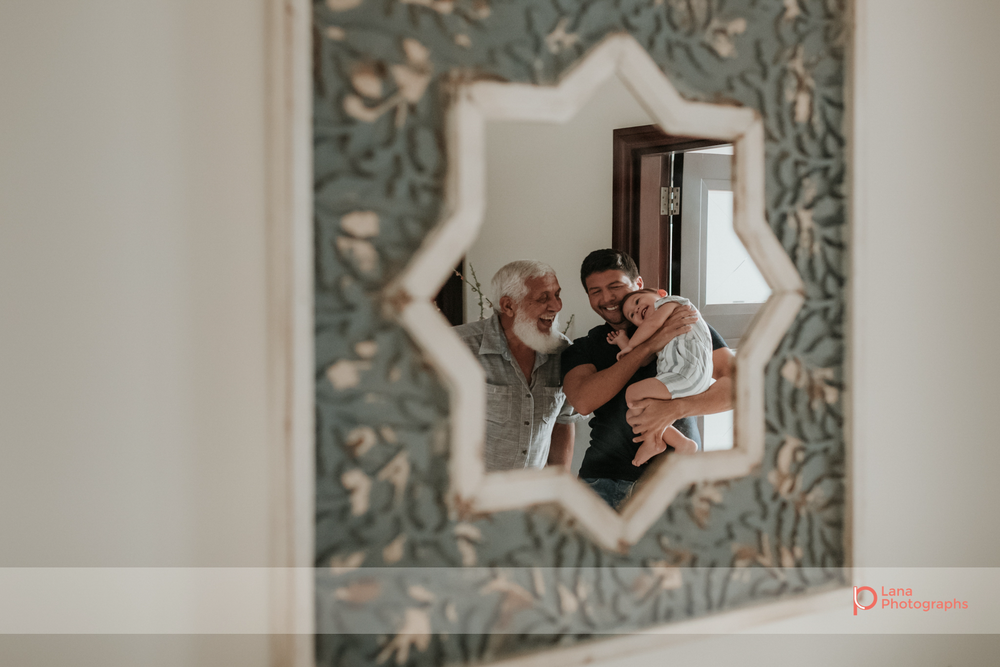 Lana Photographs Dubai Family Photographer image of three generations through a mirror, father daughter and grandpa