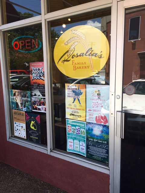 Rosalia's Family Bakery window filled with posters about local events.