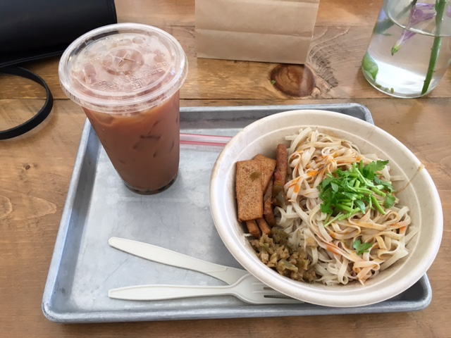 Noodle bowl with tofu, spicy sauce, and cilantro. Bubble tea to drink.