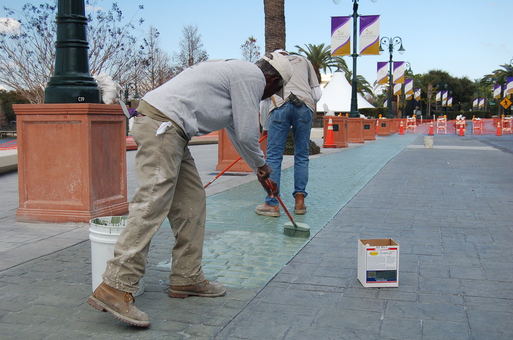 Workers apply FreestylePRO to a stamped concrete streetscape at an amusement park. This application will periodically be recolored with FreestylePRO.