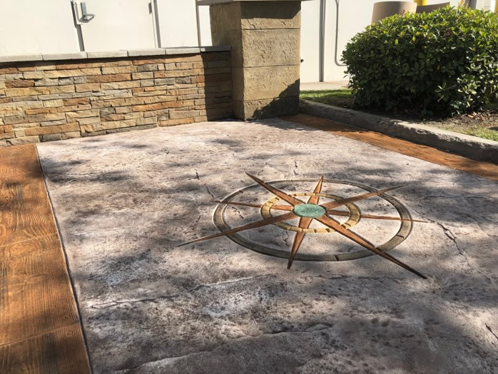 The finished product - featuring stamped overlay, a stenciled and stained compass rose, and a textured and colored wall - will serve as a lasting demonstration tool for the location.