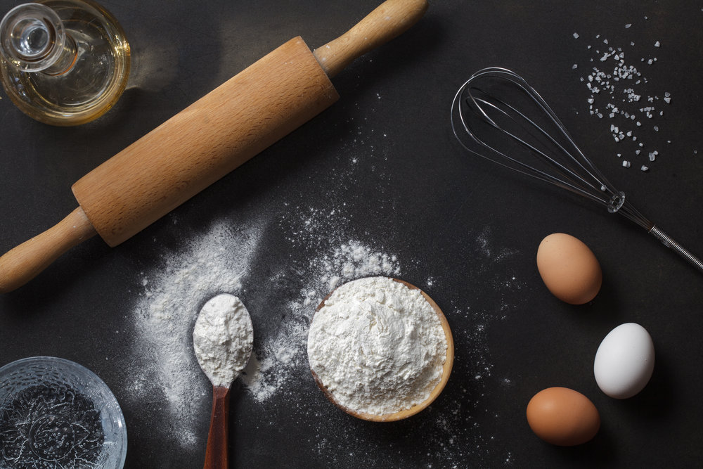 stock-photo-flour-and-ingredients-on-black-table-top-view-283115153.jpg
