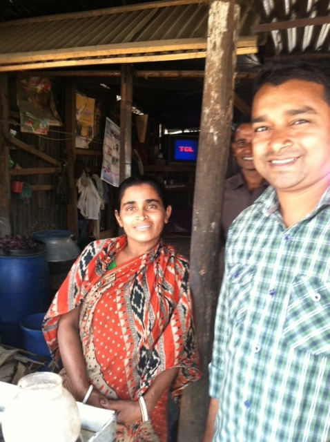 Sajal standing next to our tea stall loan recipient.JPG