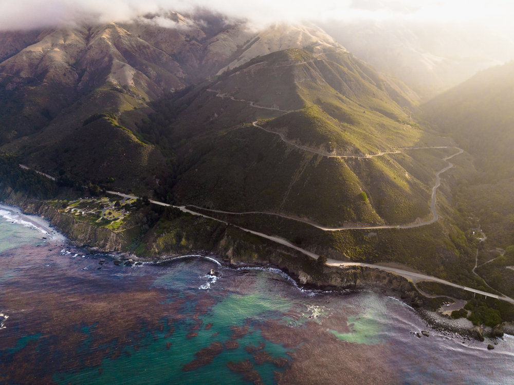 Big Sur's opalescent seascape with Kirk Creek Campground (left) and Nacimiento-Fergusson Road snaking up into the hills. Photo: @francisfraioli