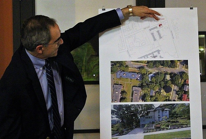 Stephen Brown shows neighbors a map and photographs of 320 Canner St., a two-story, single-family home that Yale is interested in purchasing and converting to academic use.