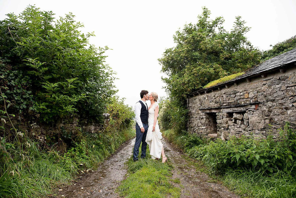 Couple kissing in the middle of a country road