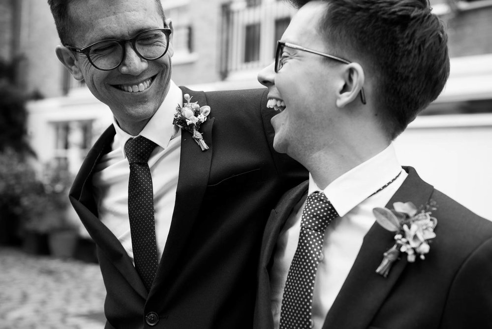 Gay wedding couple laughing together