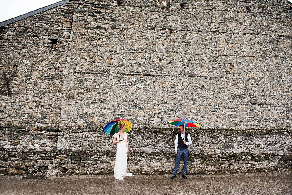 Couple posing with rainbow umbrellas