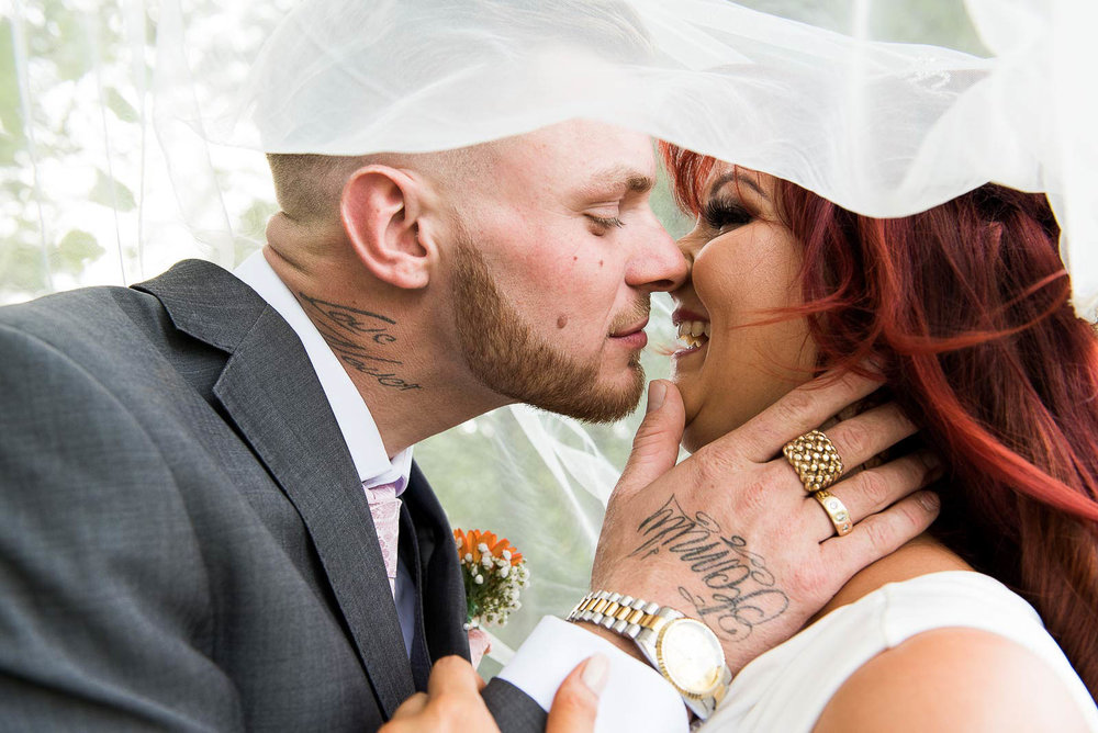 Tattooed couple sharing a kiss